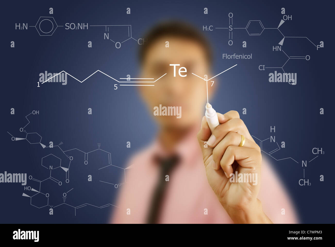 Asian teacher writing scientific formula on the whiteboard. - Stock Image