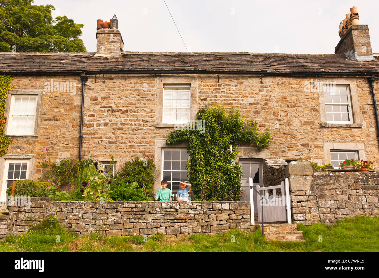 Two brothers sitting outside their holiday cottage in Low Row in Swaledale in North Yorkshire , England , Britain - Stock Image
