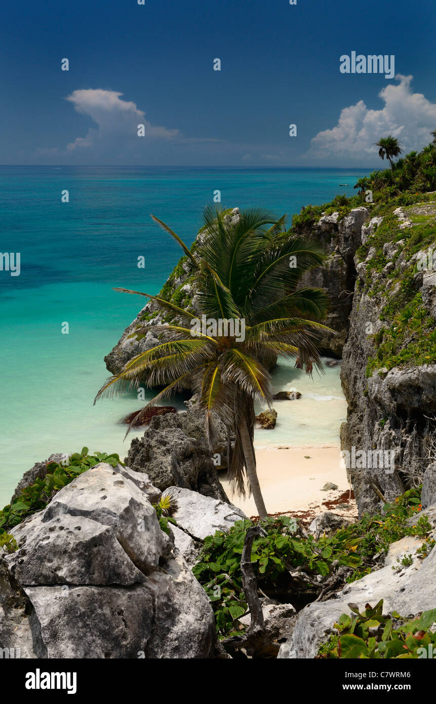 Sheer rocky sea cliffs and sand beach at Tulum in the Caribbean Gulf of Mexico - Stock Image