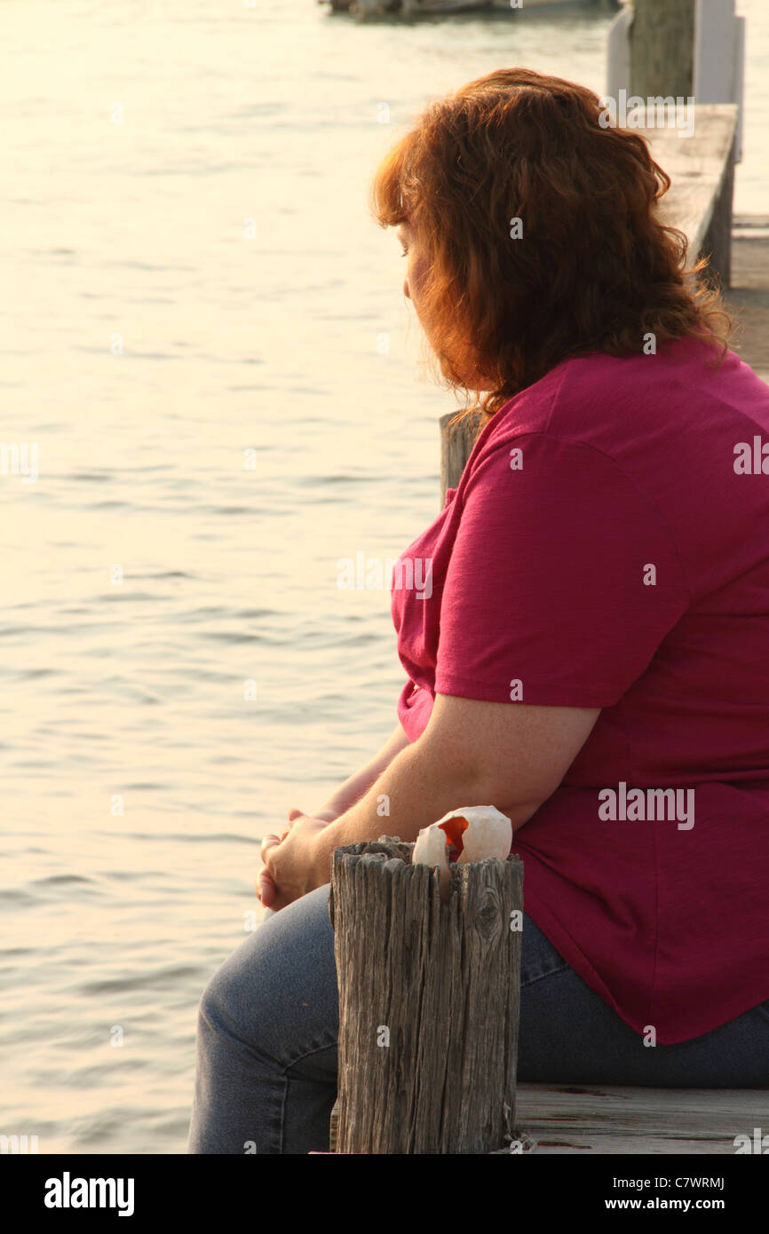 overweight adult woman depression sitting on pier Stock Photo