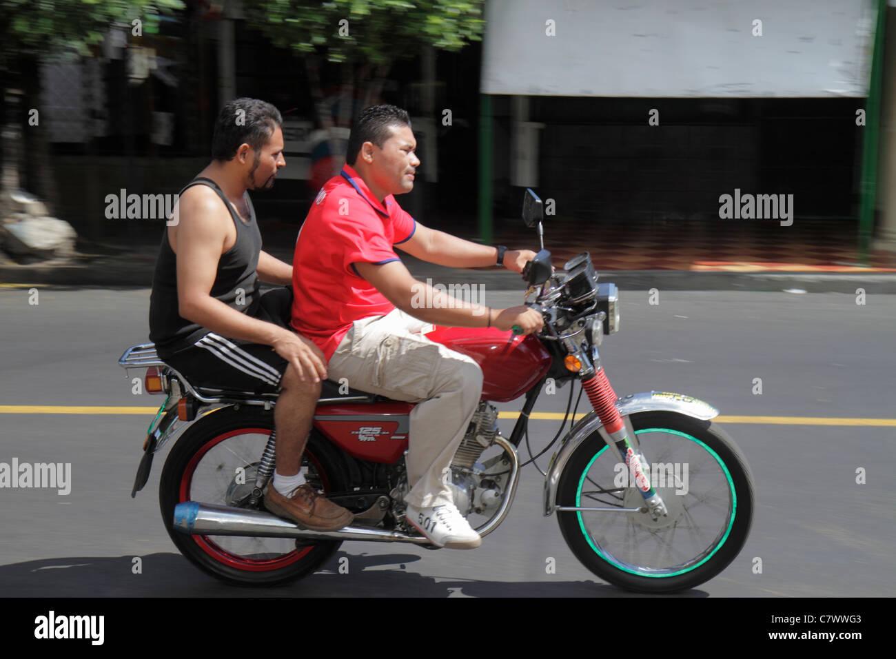 Managua Nicaragua street scene motion Hispanic man driver rider passenger motorcycle riding no helmet unsafe motion - Stock Image