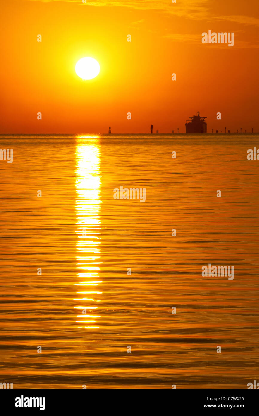 Sun rising over ocean - Stock Image