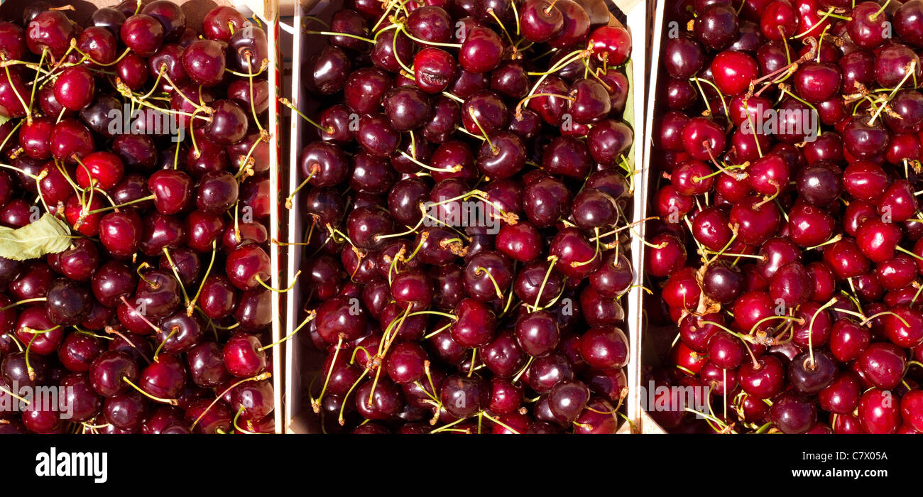 Cherry red fruits in wooden baskets at the market - Stock Image