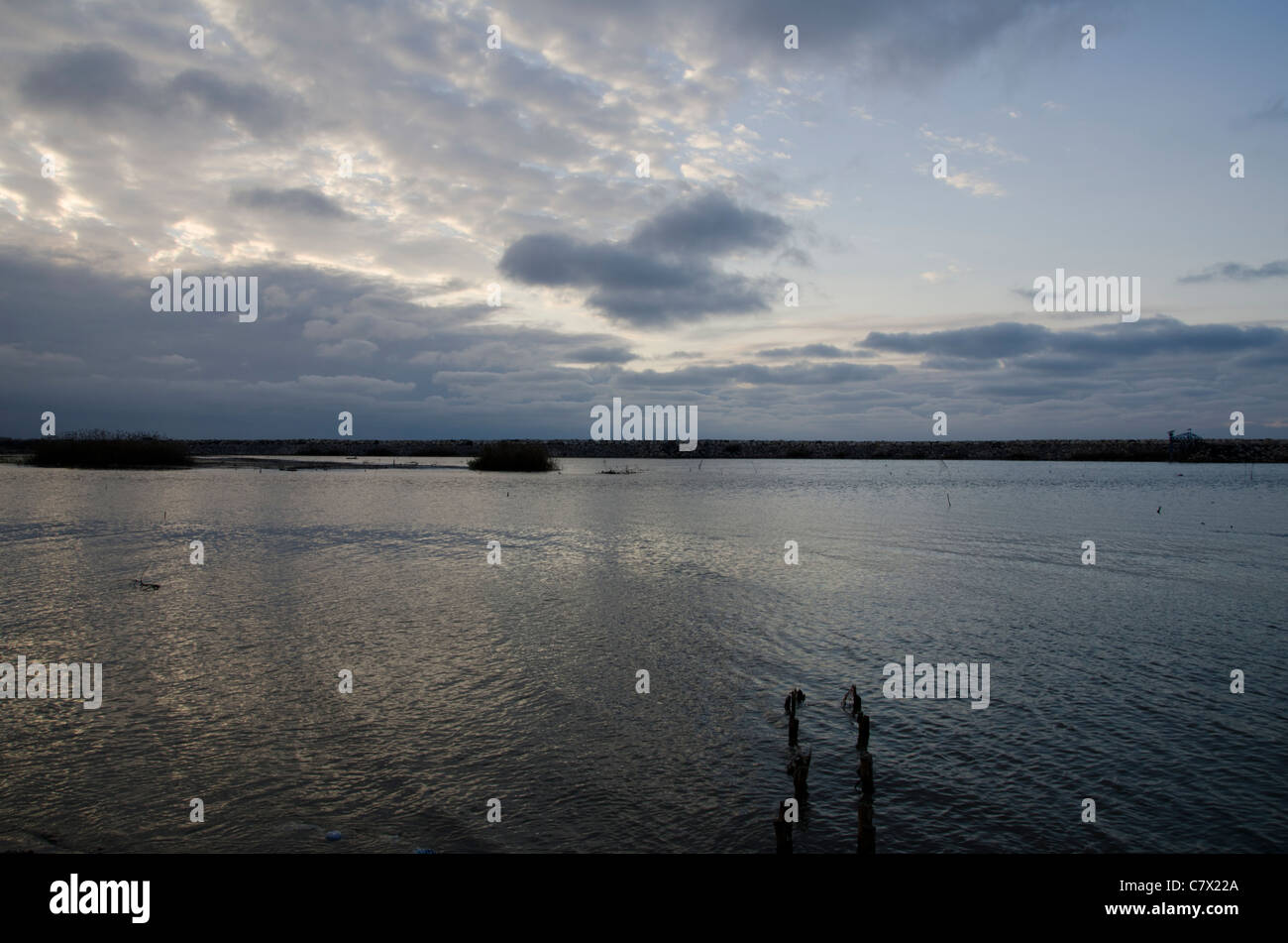 cloudy sunset at Caspian sea shore with  a broken wharf - Stock Image