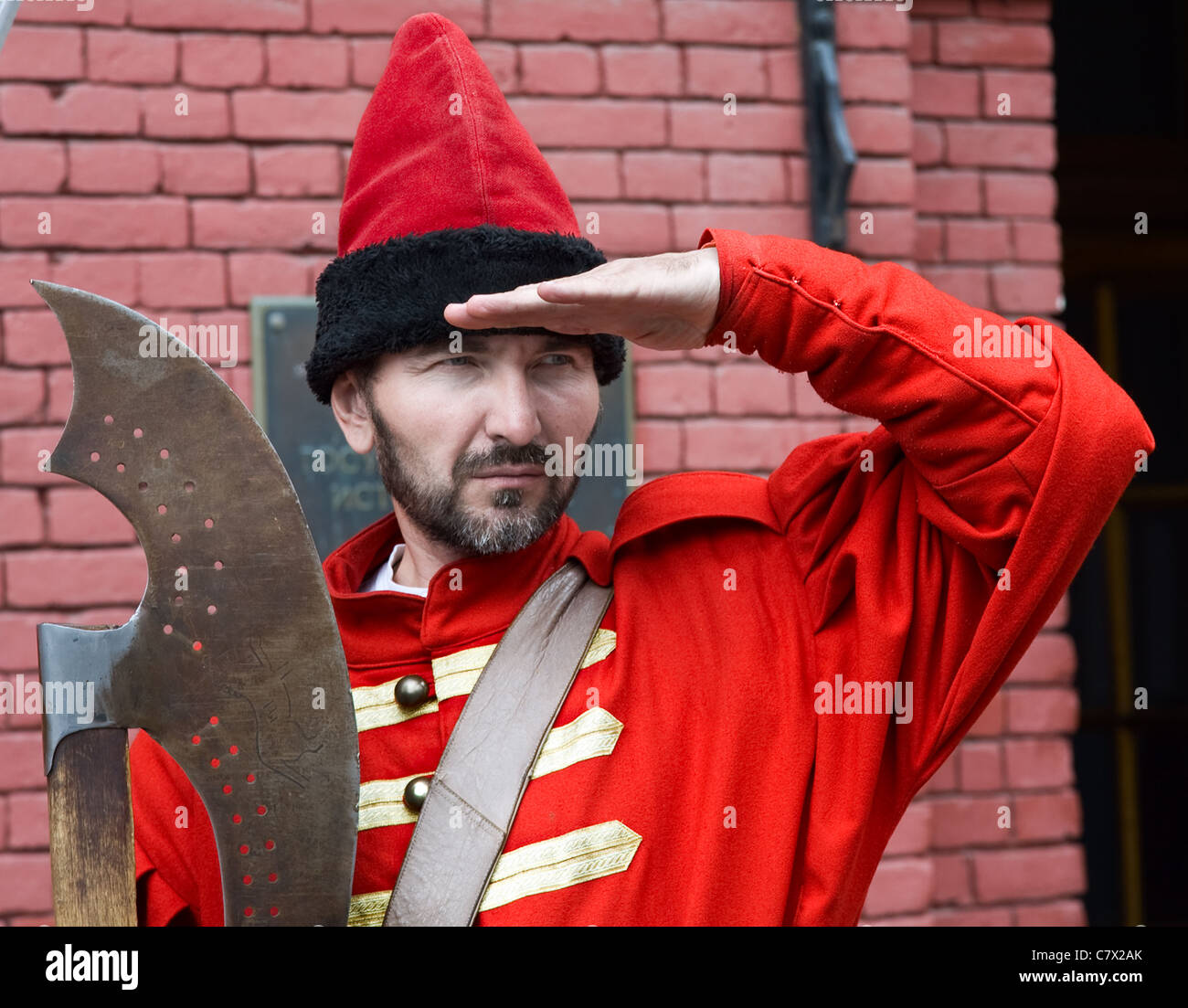 rifleman dress in  costume of red caftan and shapka with axe looking  at  frontwards Stock Photo