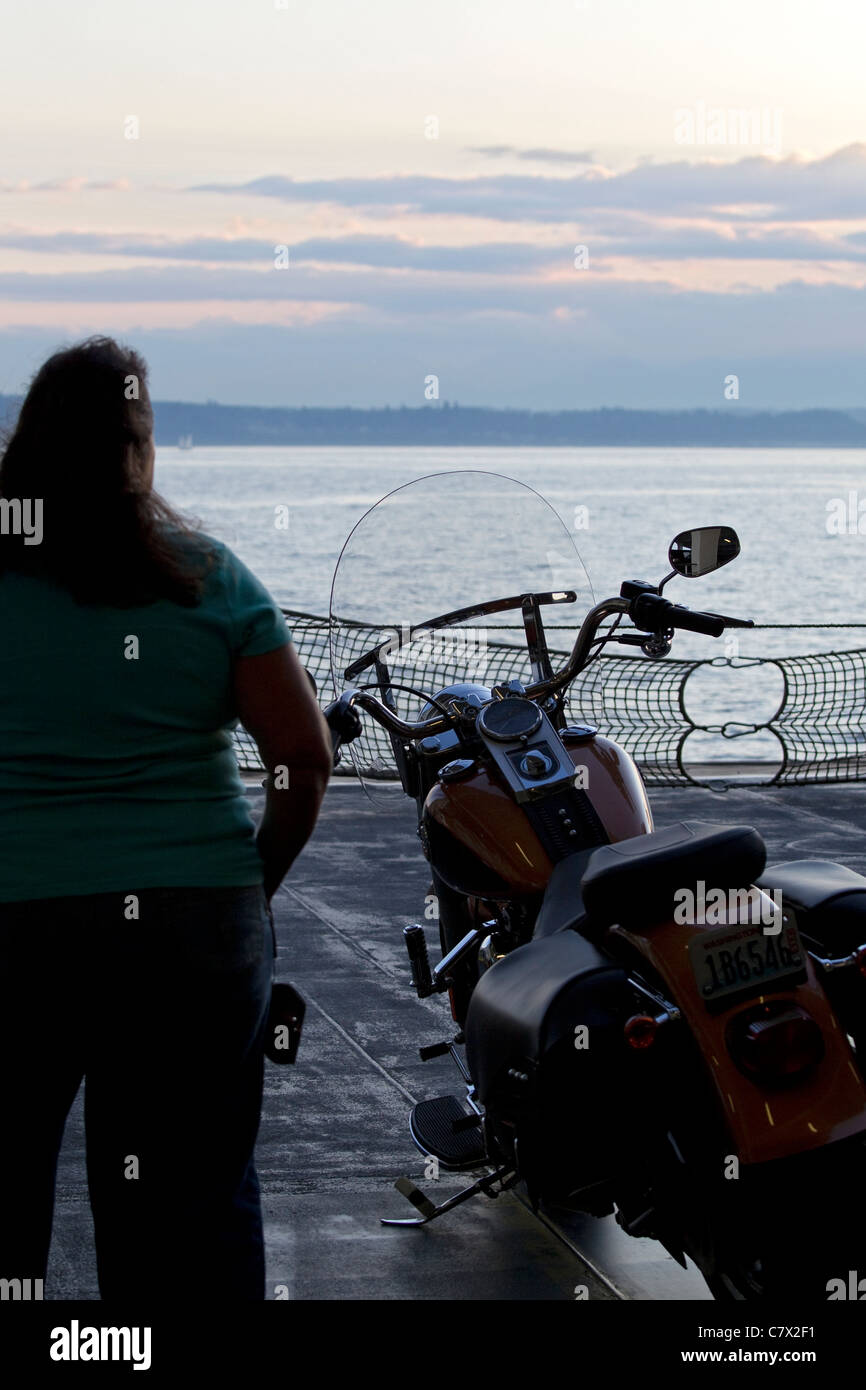 Ferry boat, woman and motorcycle cross Puget Sound on Washington State Ferry - Stock Image