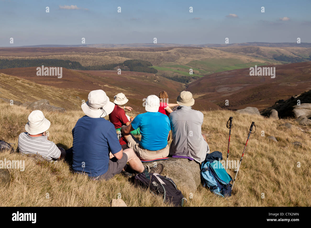 A group of walkers sitting by Fairbrook on the edge of Kinder Scout looking towards Bleaklow - Stock Image