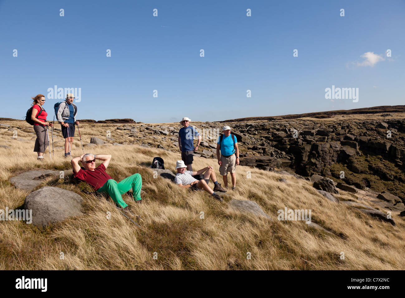 Walkers resting in the sunshine by Kinder Downfall on the edge of Kinder Scout in the Peak District National Park, - Stock Image