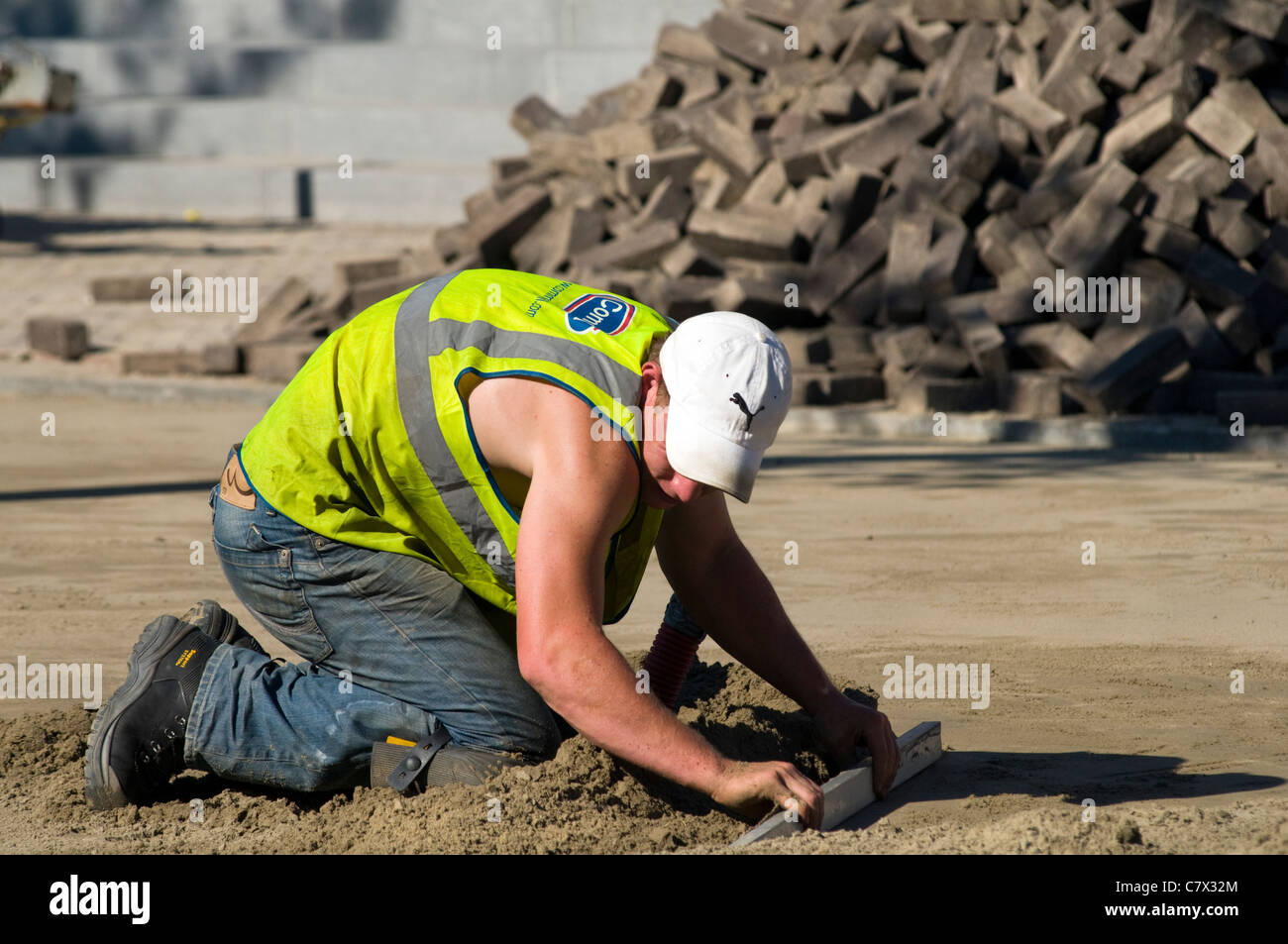 A workman laying new paving stones at a construction site during a period of hot weather - Stock Image