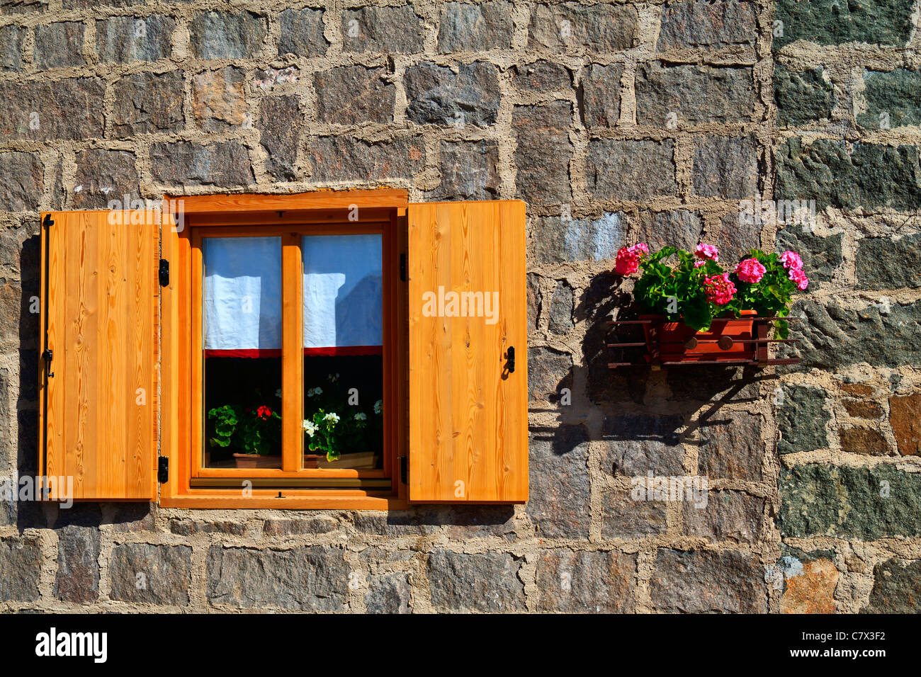 Wooden window with shutters and flower box - Stock Image