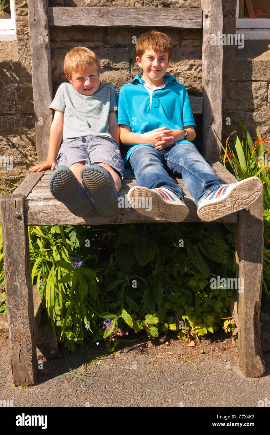 Two boys sit on the giant chair outside the Old School Crafts Shop at Muker in Swaledale in North Yorkshire , England Stock Photo