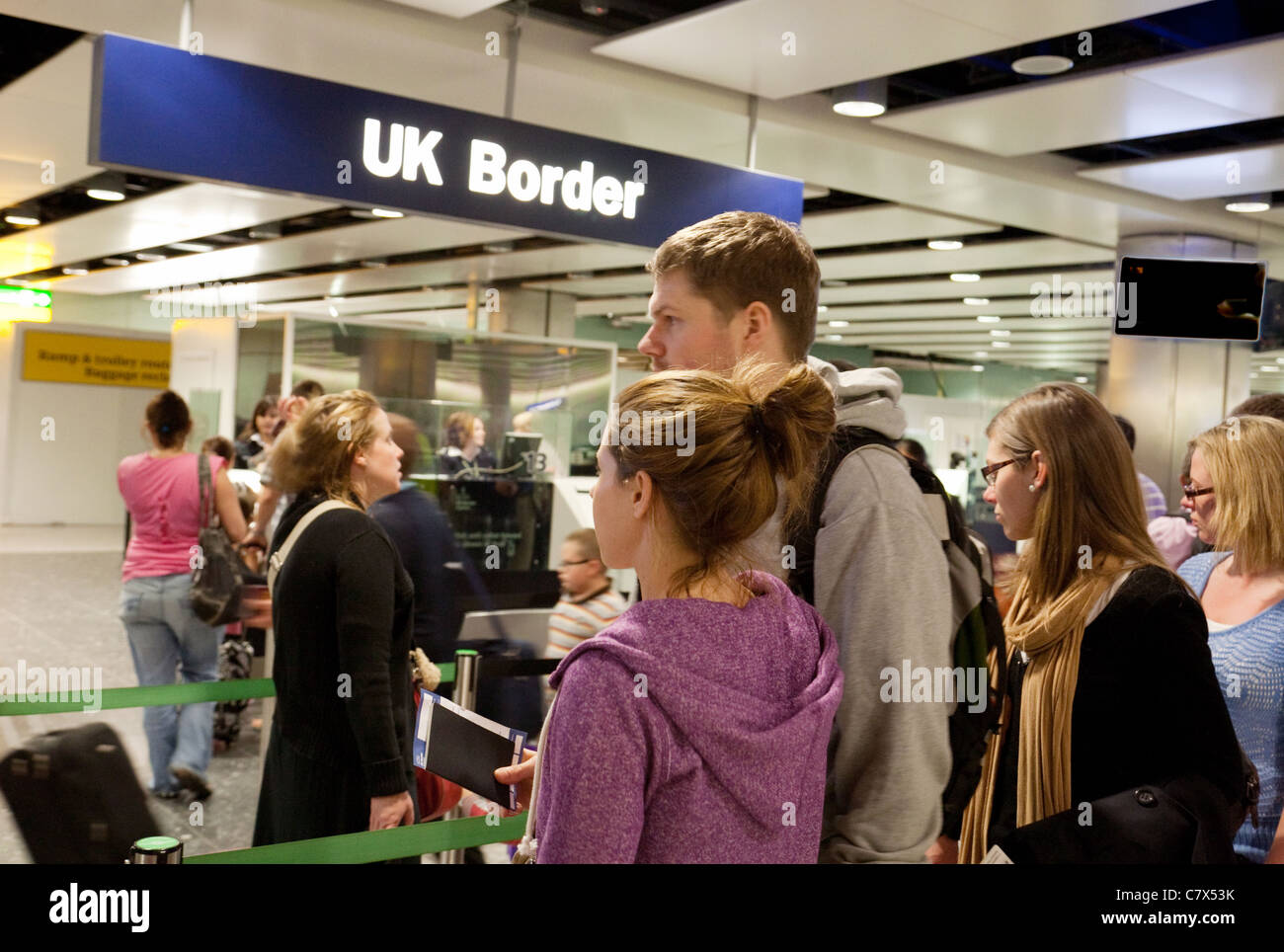 Young people waiting to enter the UK Border at immigration, Terminal 3, Heathrow airport, London - Stock Image