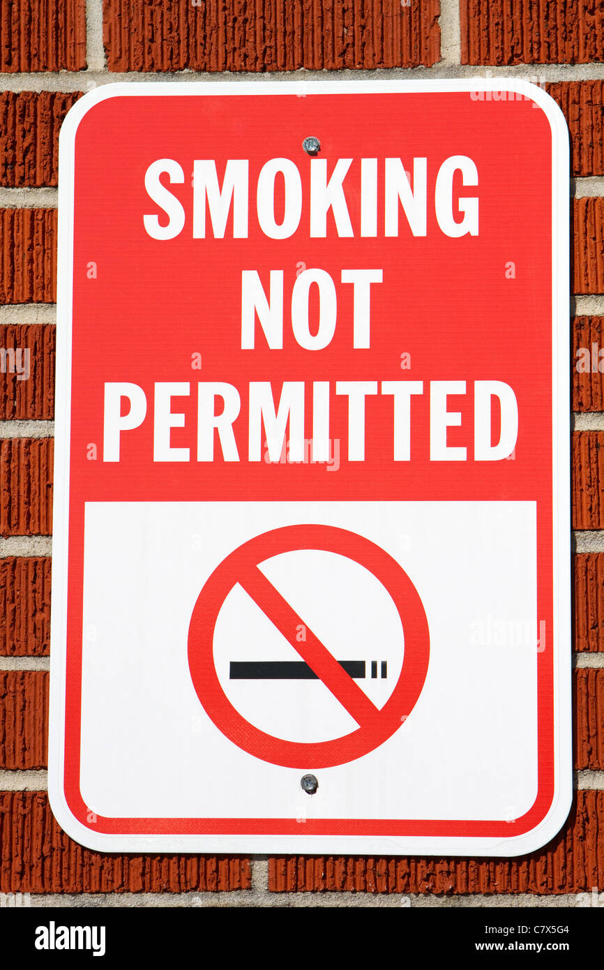 Sign hangs on a brick wall warning that smoking is not permitted in the area. - Stock Image