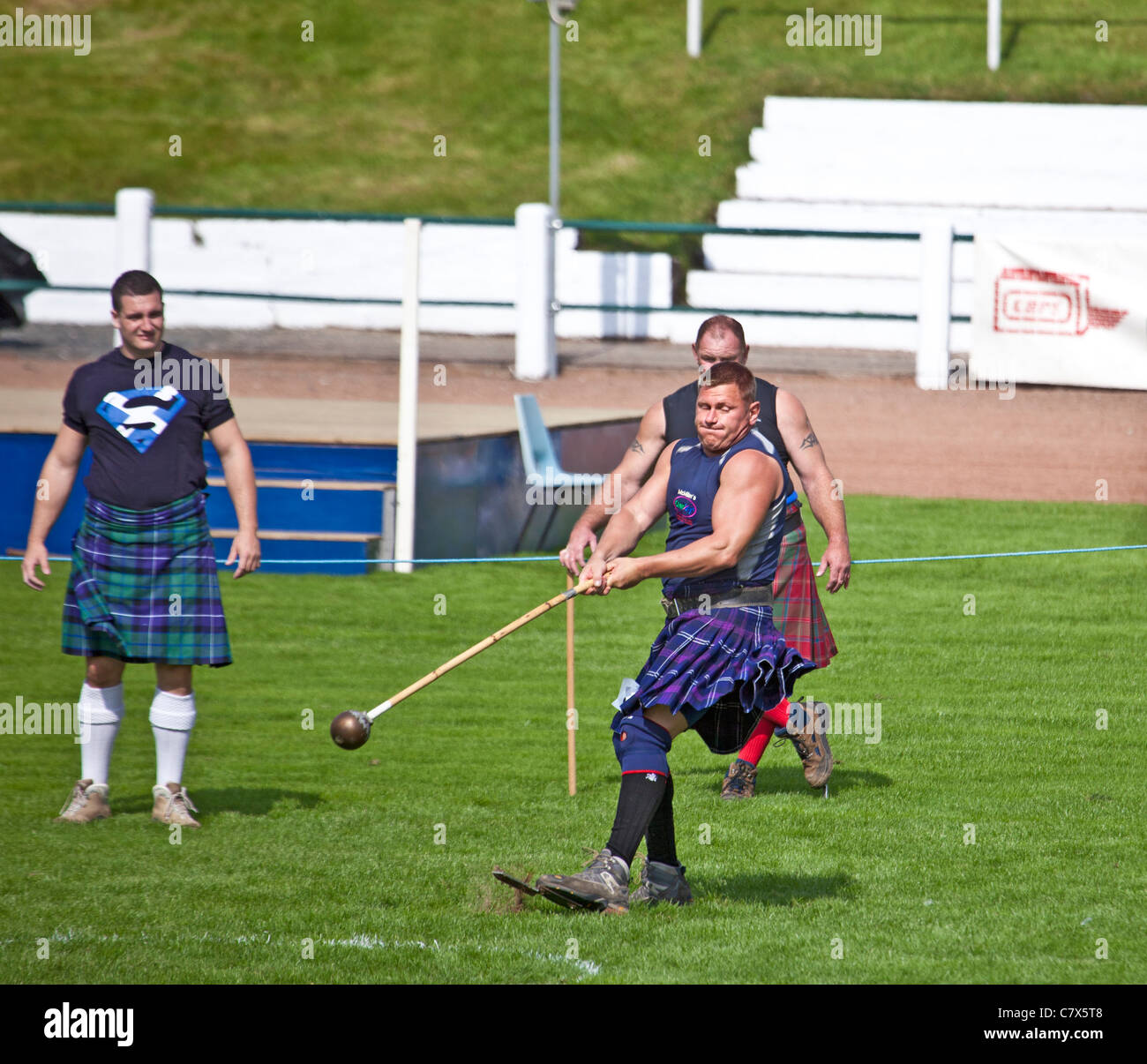 'Heavy' athlete throwing the hammer at Cowal Highland Gathering, 2011 with fellow competitors watching. - Stock Image