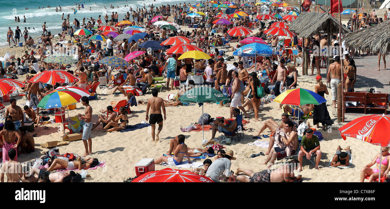 Summer vacation. holiday maker on a crowded beach. Photographed at Nitsanim Beach, Israel Stock Photo
