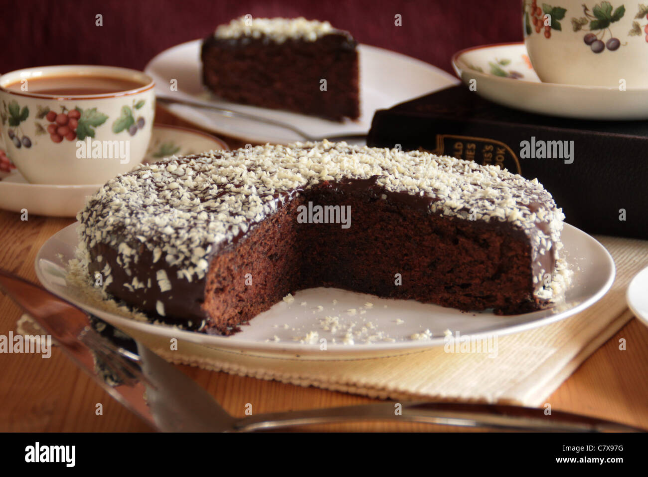 Rich dark chocolate cake on a porcelain plate - Stock Image