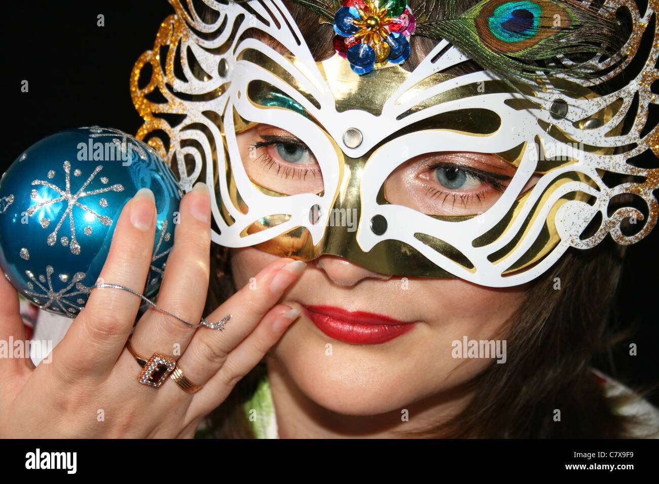 Portrait of attractive beautiful young woman wearing carnival mask - Stock Image