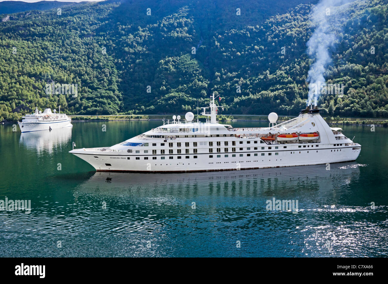 Cruise ships Athena (moored left) and Seabourn Pride (turning to leave) on the Aurlandsfjorden at Flaam in Western - Stock Image