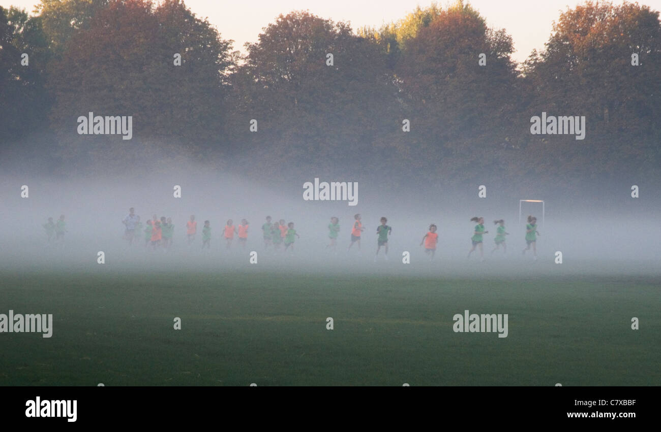 School children running on misty morning, Wandsworth Common, London UK - Stock Image