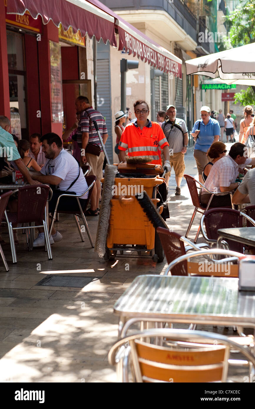 Woman Pavement sweeper passing sidewalk cafe Valencia Spain Stock Photo