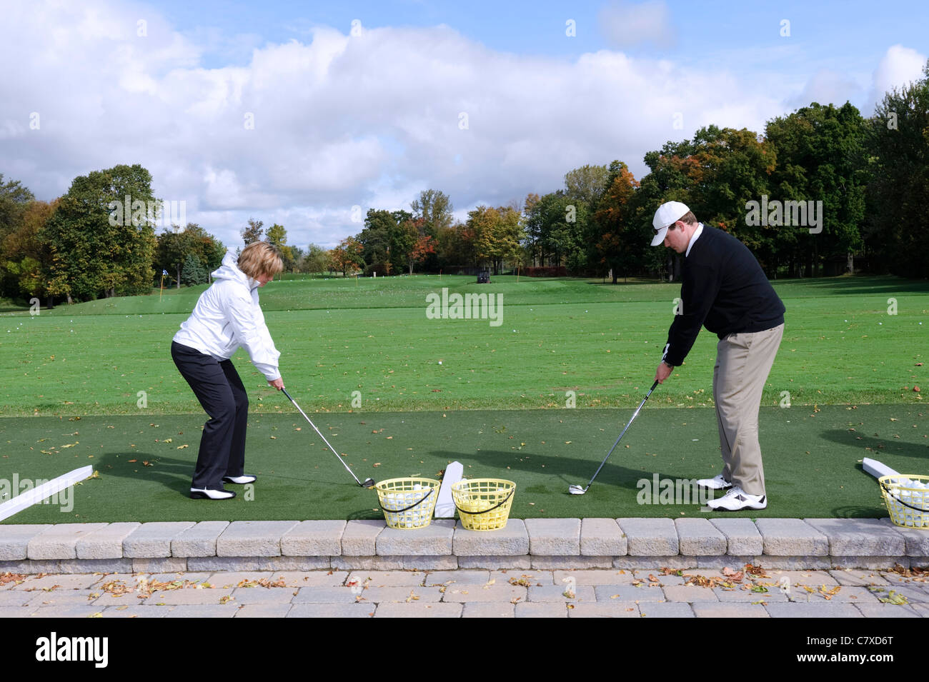 Two golfers at address position on a driving range. - Stock Image