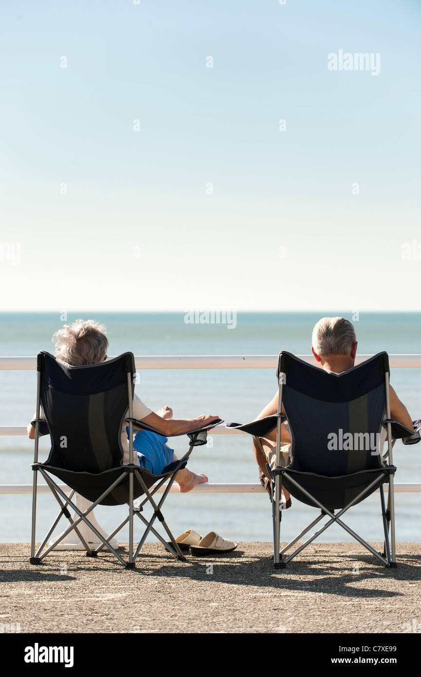 a man woman senior couple sitting in canvas folding chairs enjoying the late september 2011 heatwave, aberystwyth - Stock Image