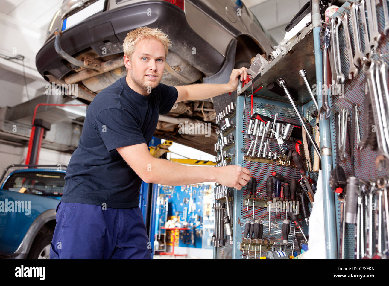 Mechanic standing beside tool chest, looking at the camera - Stock Image
