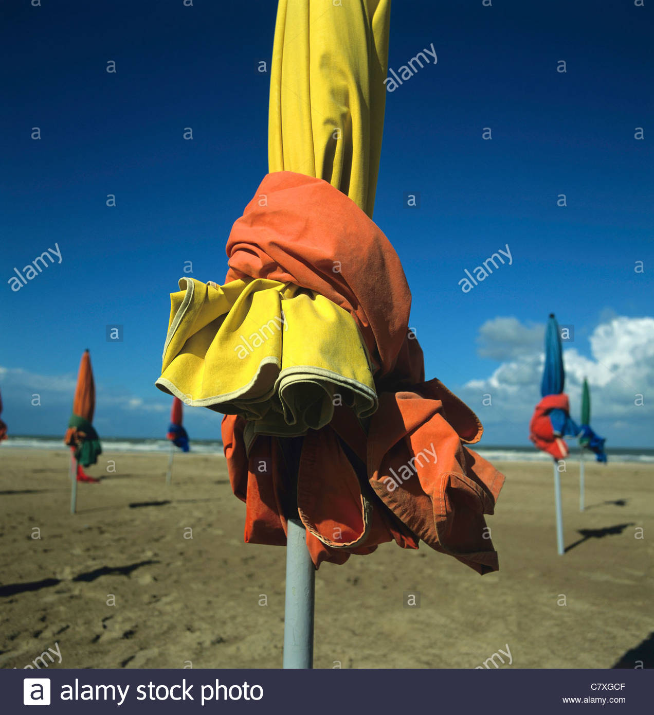 Parasol tied up out of season on beach - Stock Image