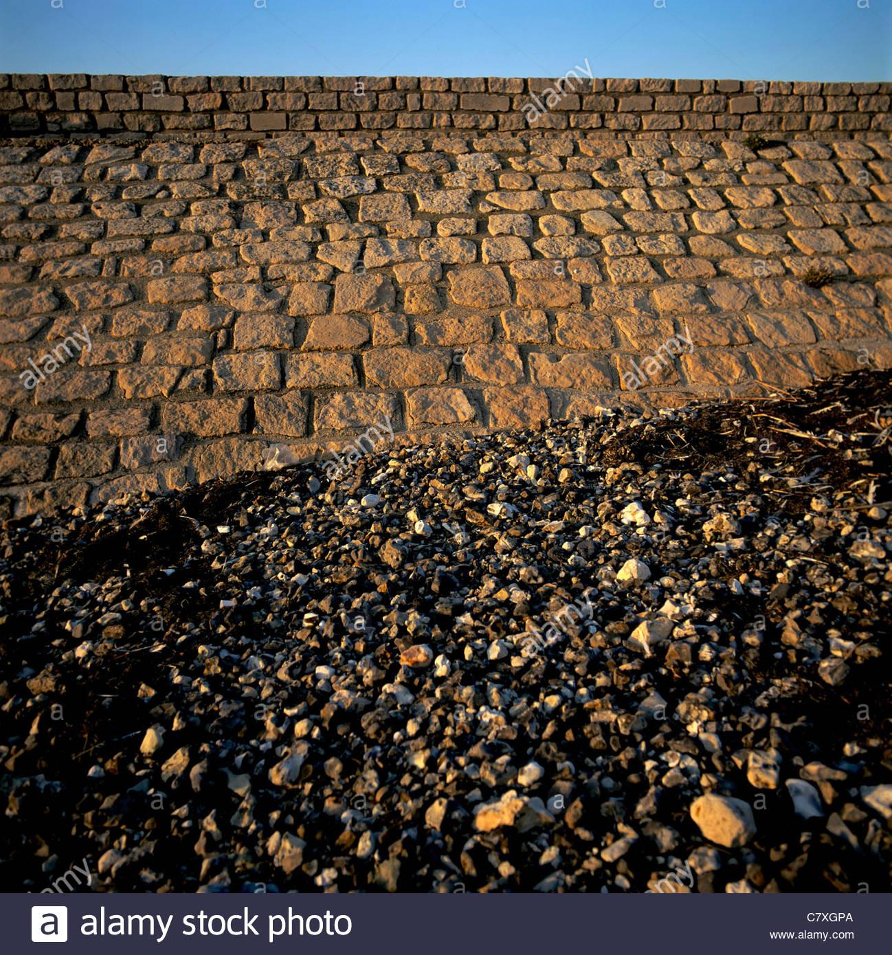 Sea wall and pebbles on beach - Stock Image