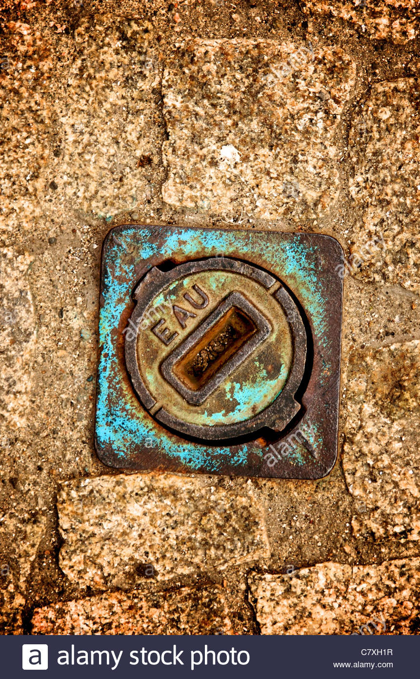 Manhole covers in a road - Stock Image