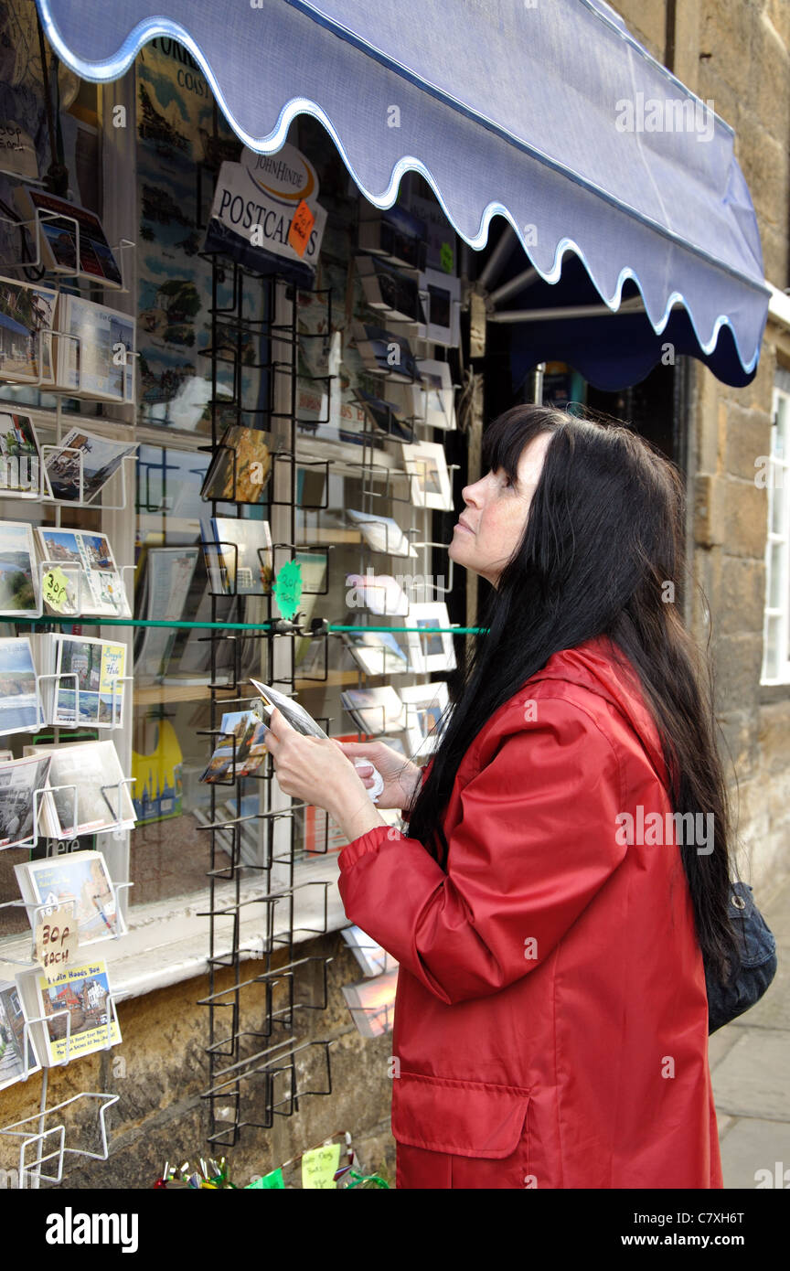 woman selecting postcards, Robin Hood's Bay, North Yorkshire, England, UK - Stock Image