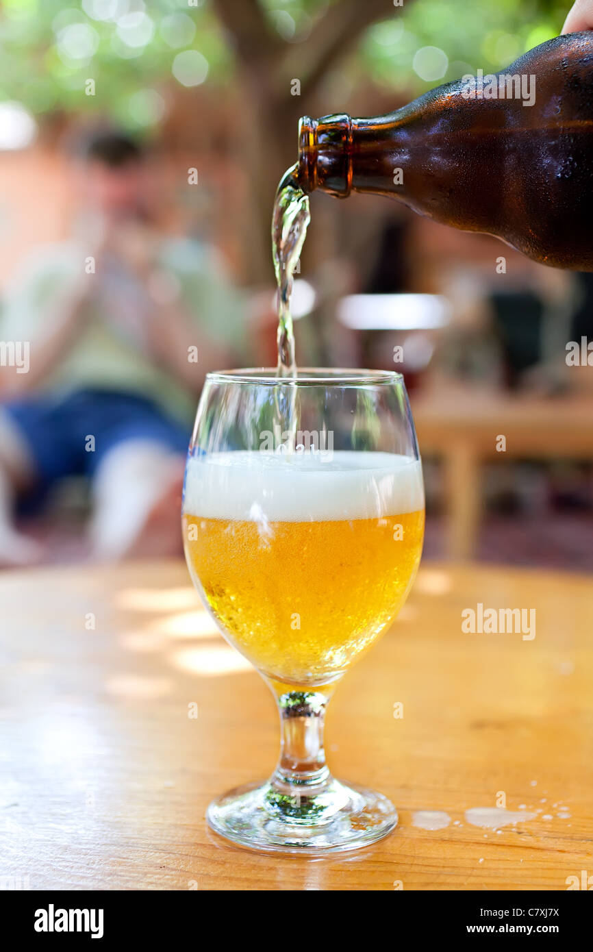 Bottle of beer flowing into the glass in outdoor bar - Stock Image