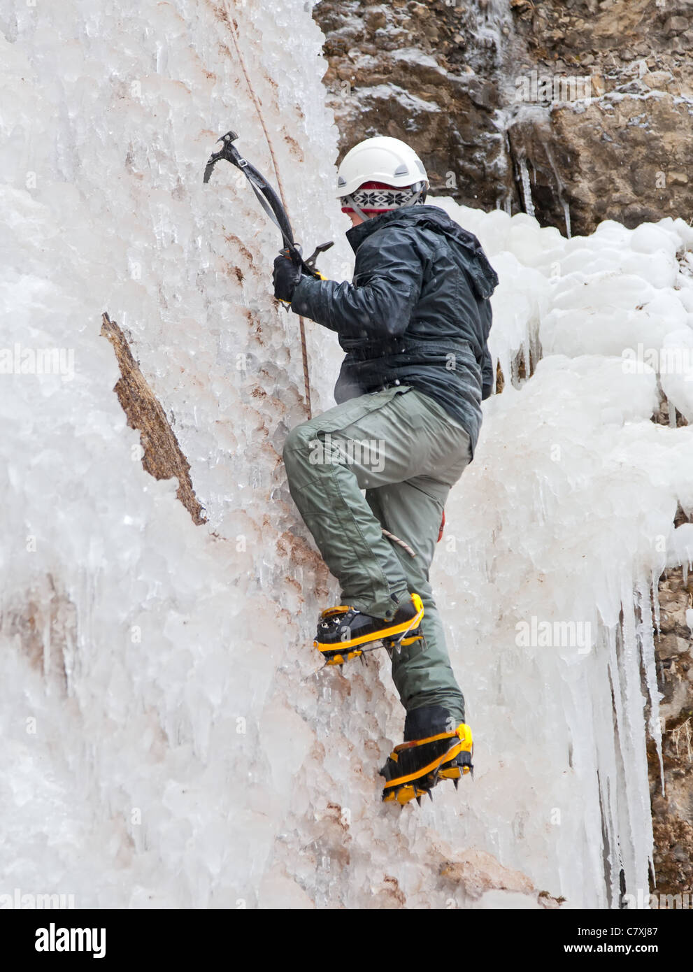 Man with ice axes and crampons climbing on icefall - Stock Image
