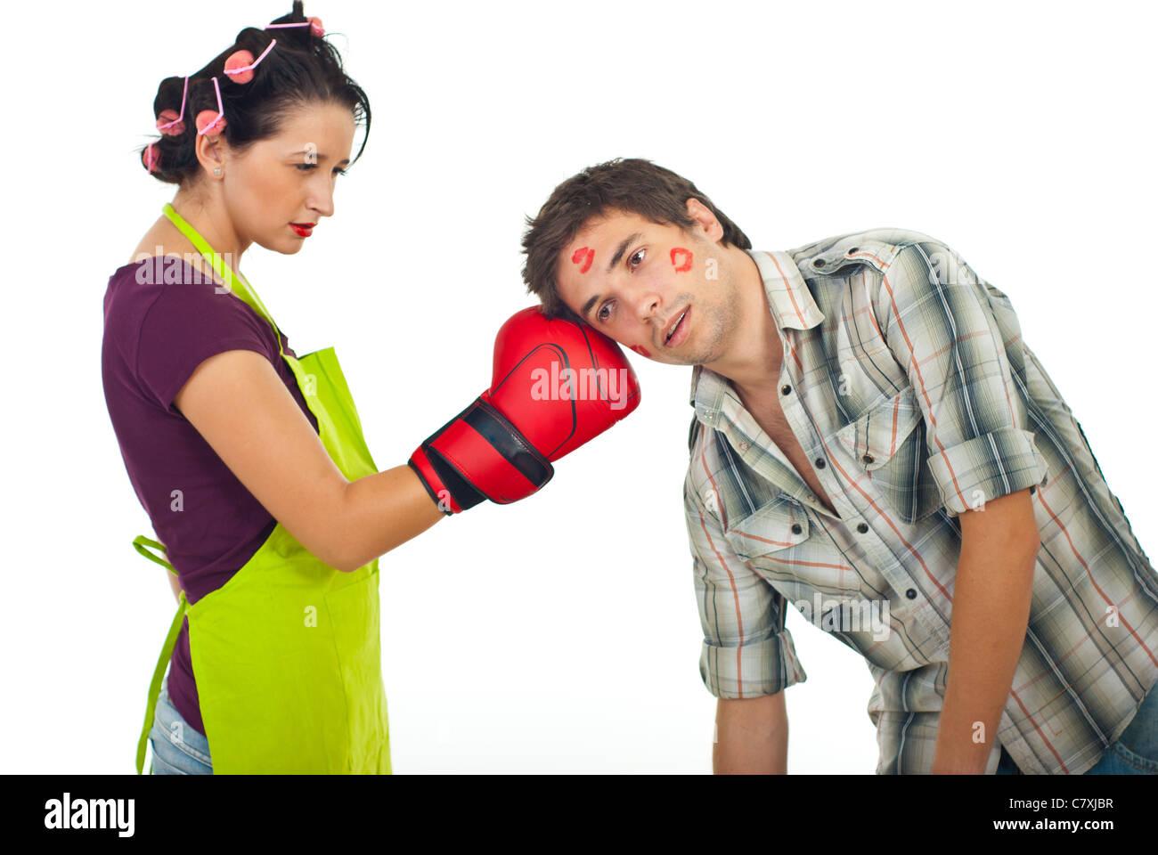Angry wife boxing unfaithful husband isolated on white background - Stock Image