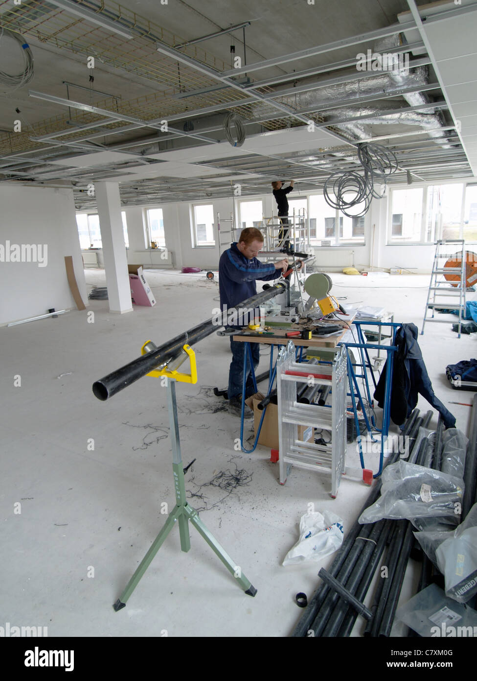 Two men installing cables and tubes in the ceiling of a brand new office building Stock Photo