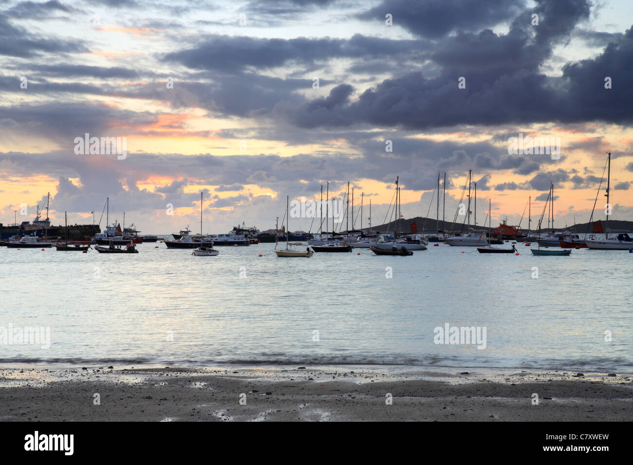 Hugh Town harbour from Porth Mellon Beach, St Marys, Isles of Scilly, Cornwall, stormy sunset - Stock Image