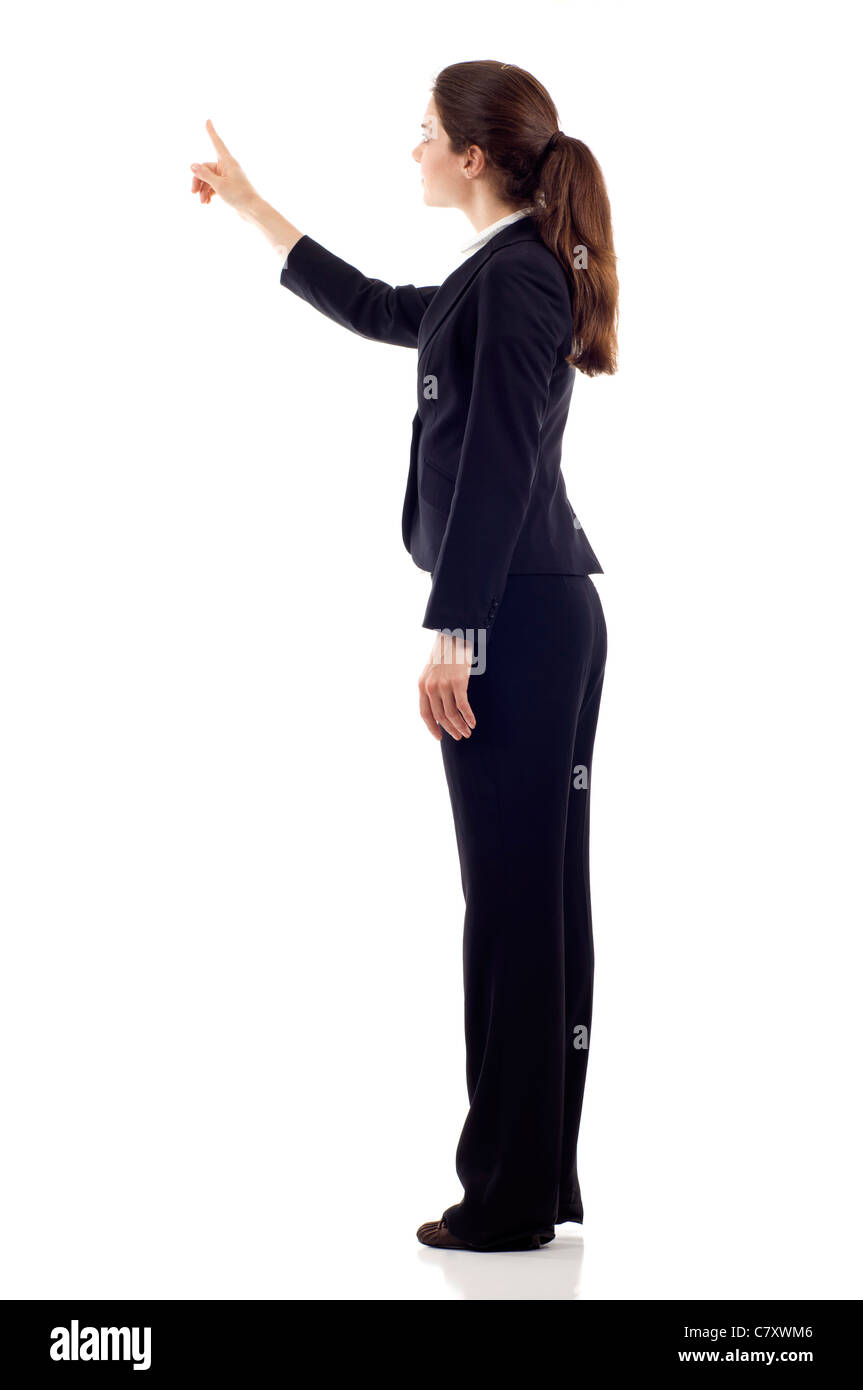 Full body of young business woman pointing at something from the back, isolated over white background - Stock Image