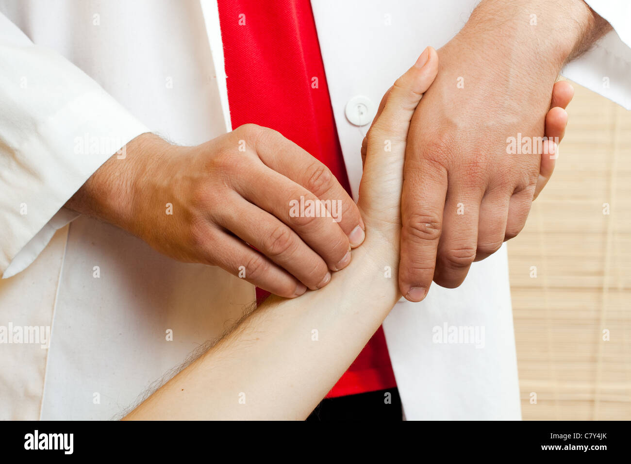 Doctor checking a patients pulse - Stock Image