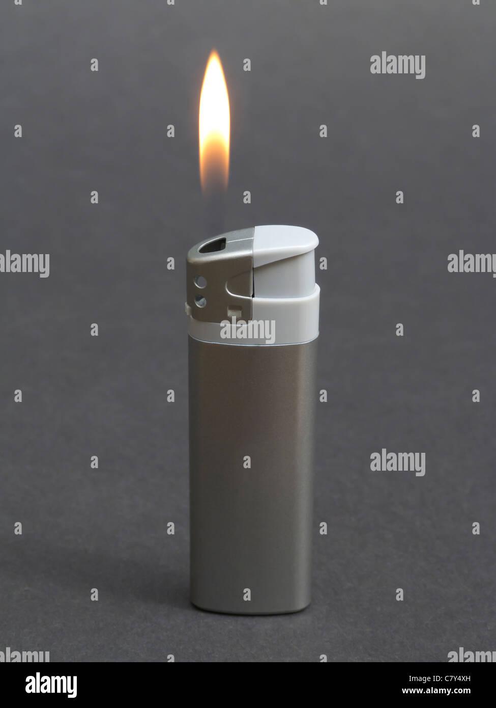 Lit Silver Lighter - Stock Image