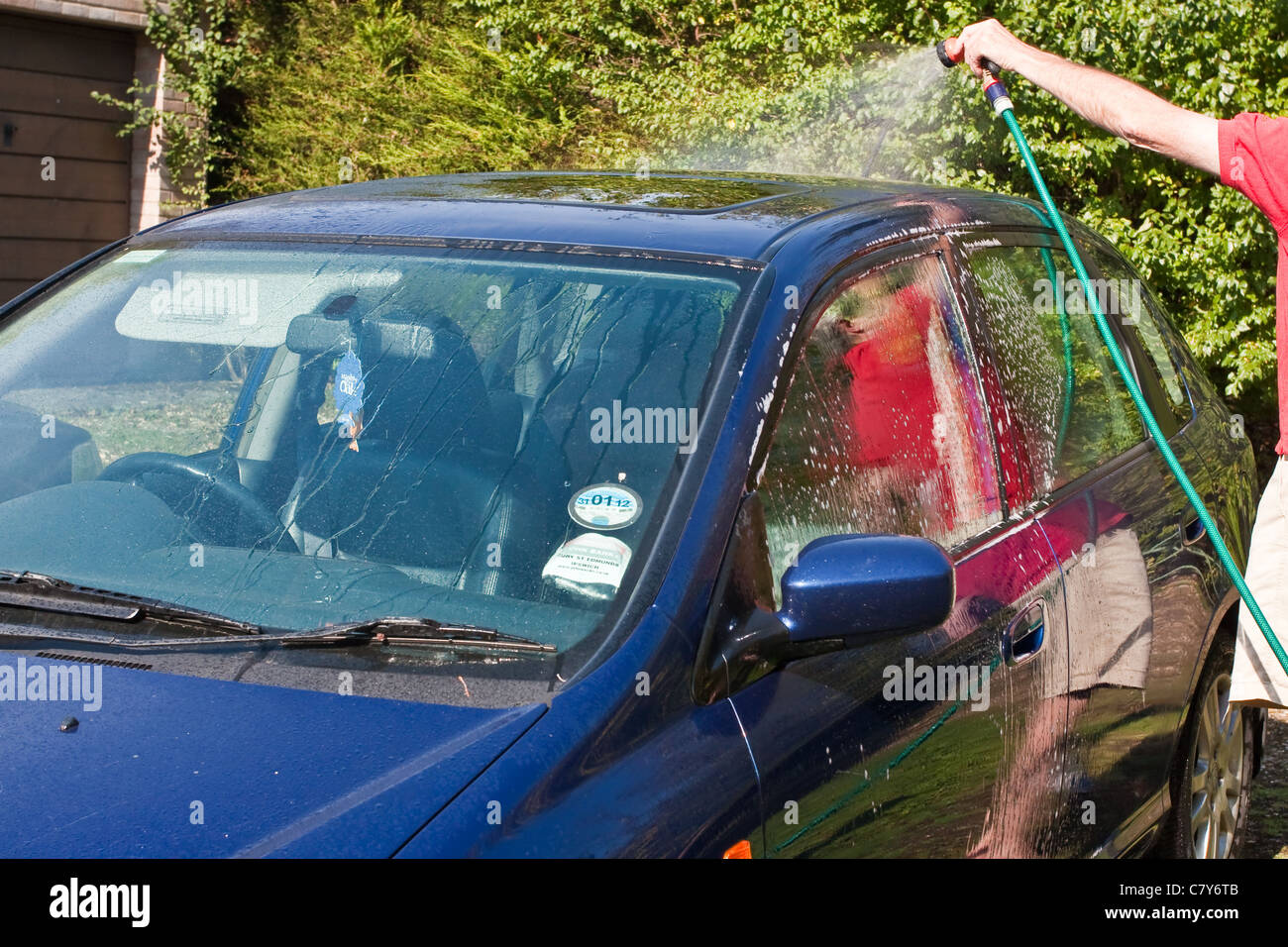 A man washing a car  during the October heat wave in the UK, 2011 - Stock Image