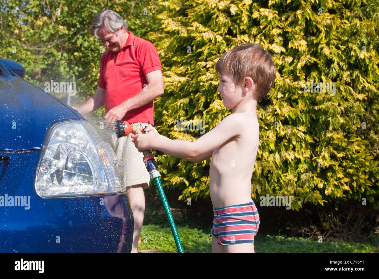Grandad and grandson washing car together during the October heat wave in the UK, 2011 - Stock Image