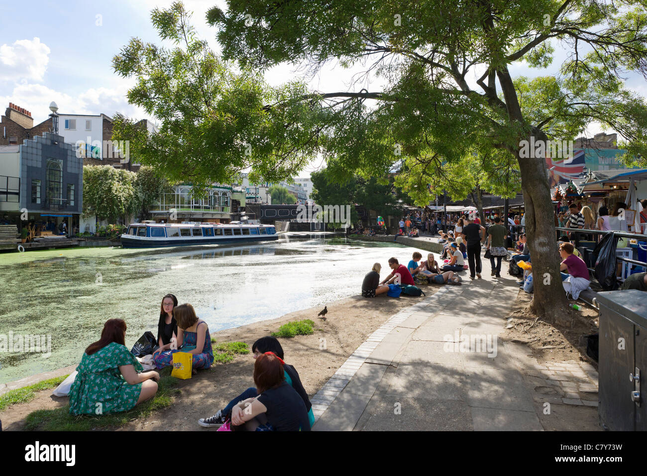 Young people sitting along the banks of the Regent's Canal at Camden Lock, North London, England, UK Stock Photo