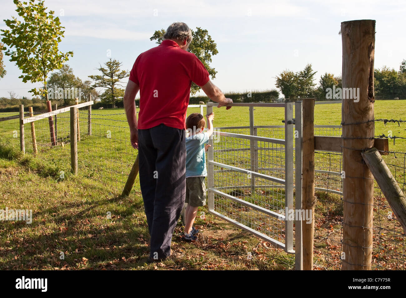 Grandad and his young grandson enjoy a walk in the country in the early October UK heat wave, 2011. - Stock Image