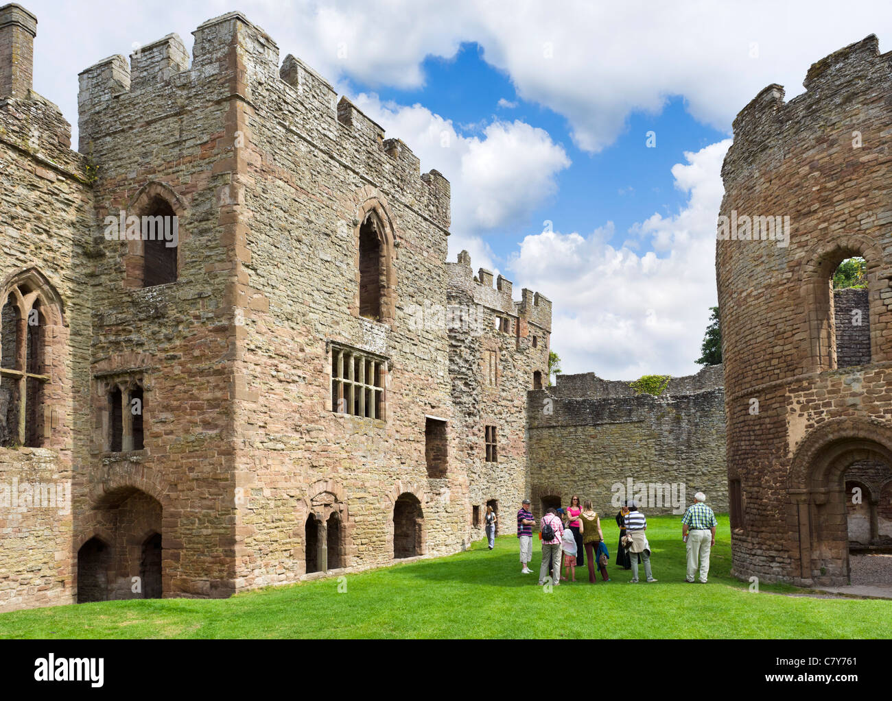 Party of tourists in the ruins of Ludlow Castle, Ludlow, Shropshire, England, UK - Stock Image