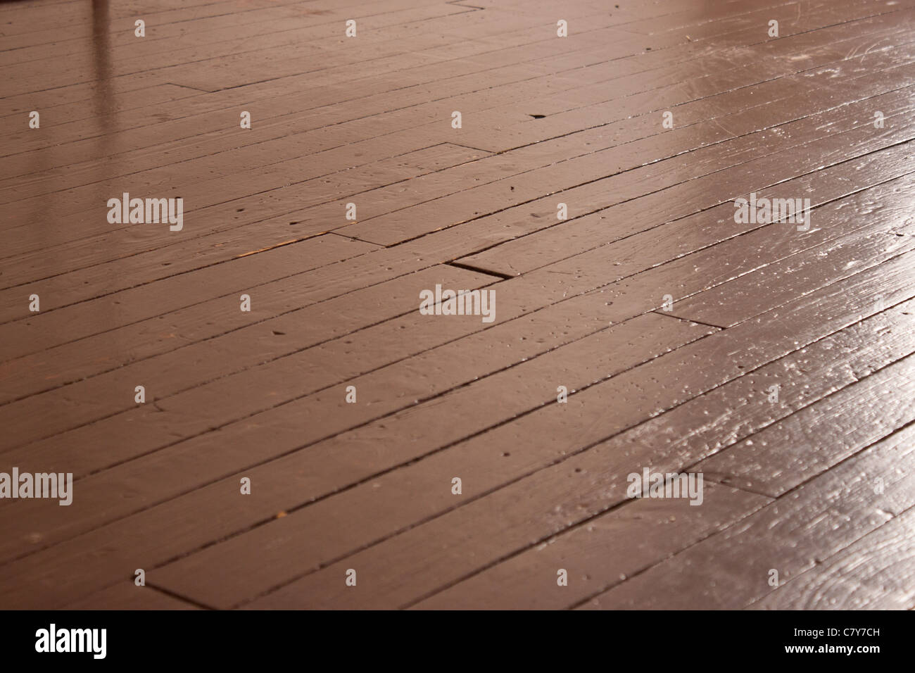 Brown painted wood flooring shining in empty room - Stock Image