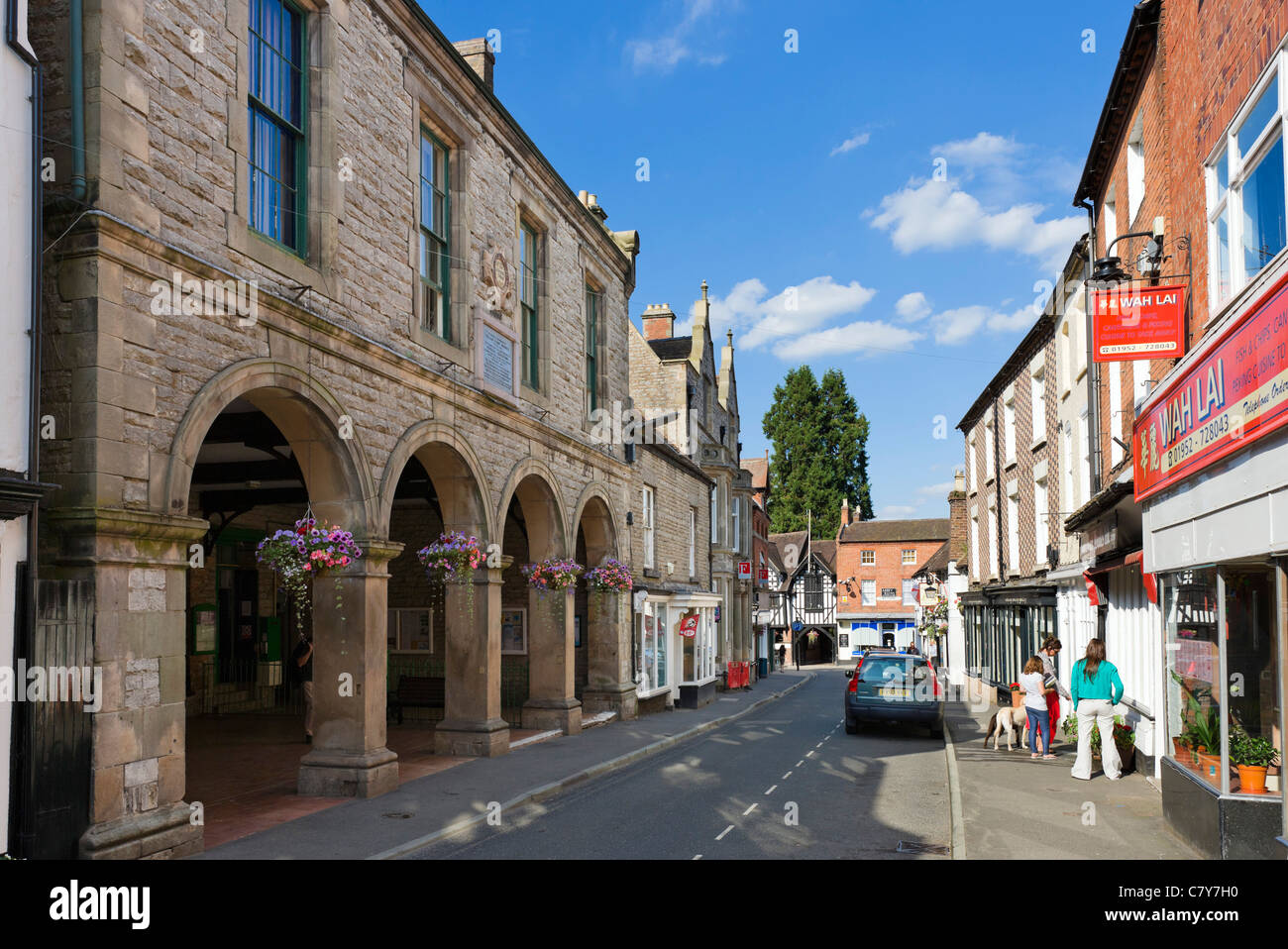 Shops on the High Street with the Corn Exchange to the left, Much Wenlock, Shropshire, England, UK - Stock Image