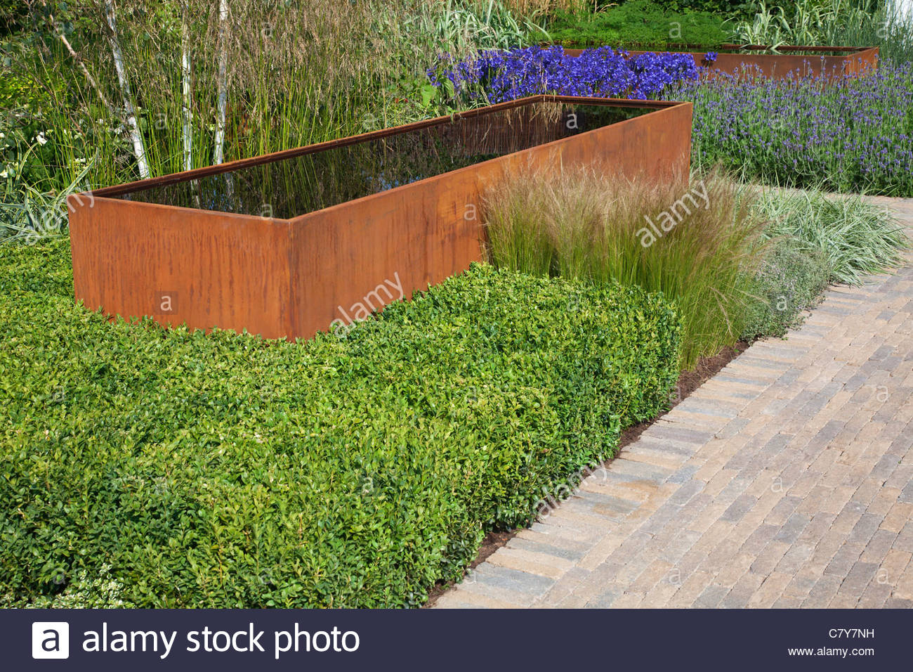 Contemporary Garden With Rusted Corten Steel Water Trough And Green Foliage  Planting. RHS Hampton Court Flower Show