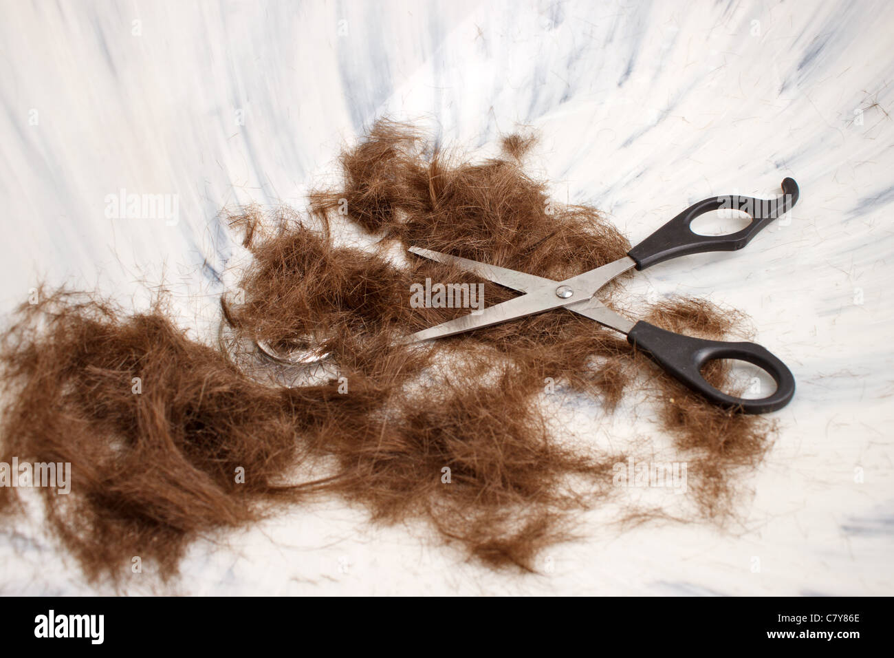 Scissors and hair clippings in marble sink after cut - Stock Image