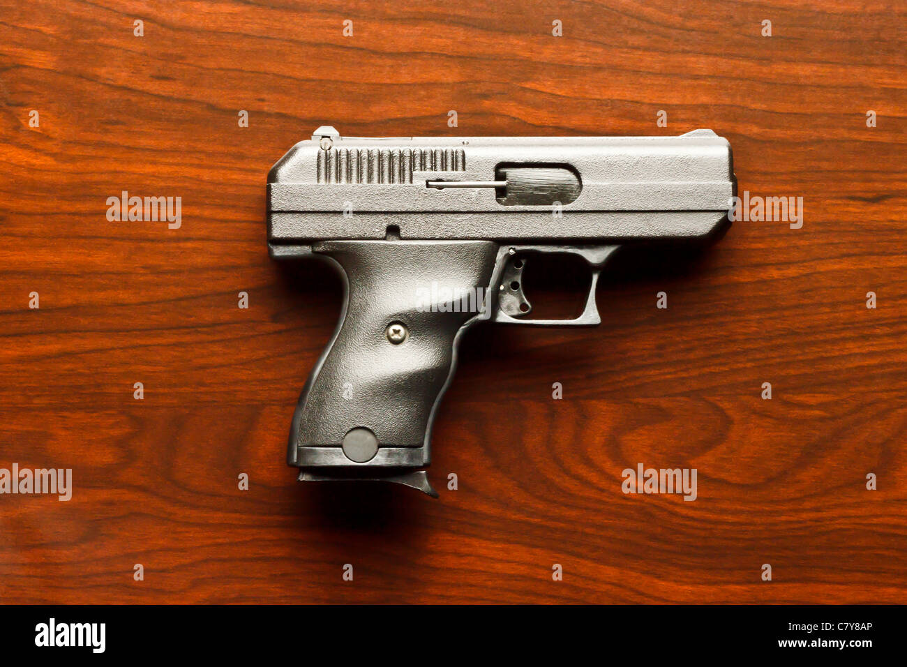 Top view of 9 mm handgun against wooden surface - Stock Image