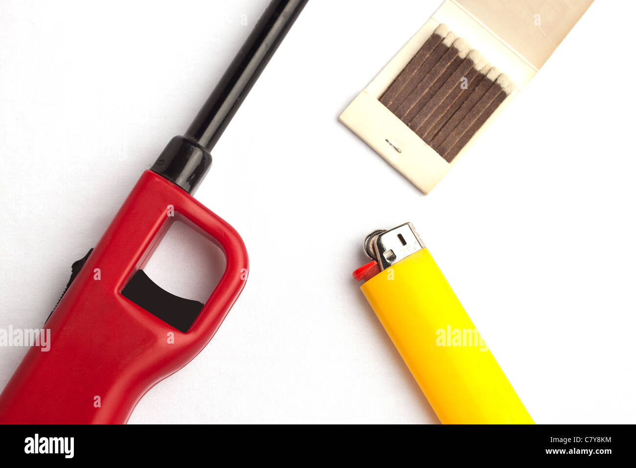 Variety of lighters against a white background including a gas lighter, disposable lighter, and matches - Stock Image